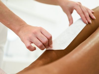 Woman having hair removal procedure on leg applying wax strip